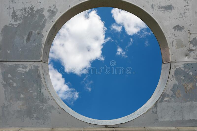Blue sky hole in aged concrete wall background.  stock photos