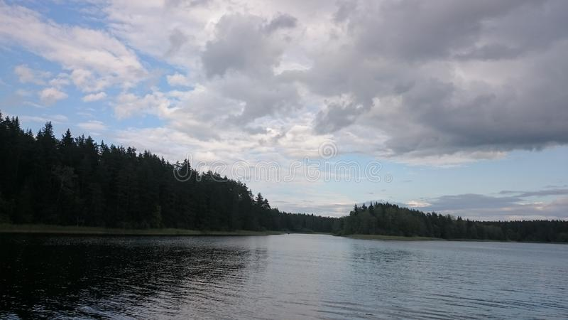 Blue sky and blue lake in summer. White clouds are reflected in the water. The famous lake Seliger. Russia royalty free stock photography