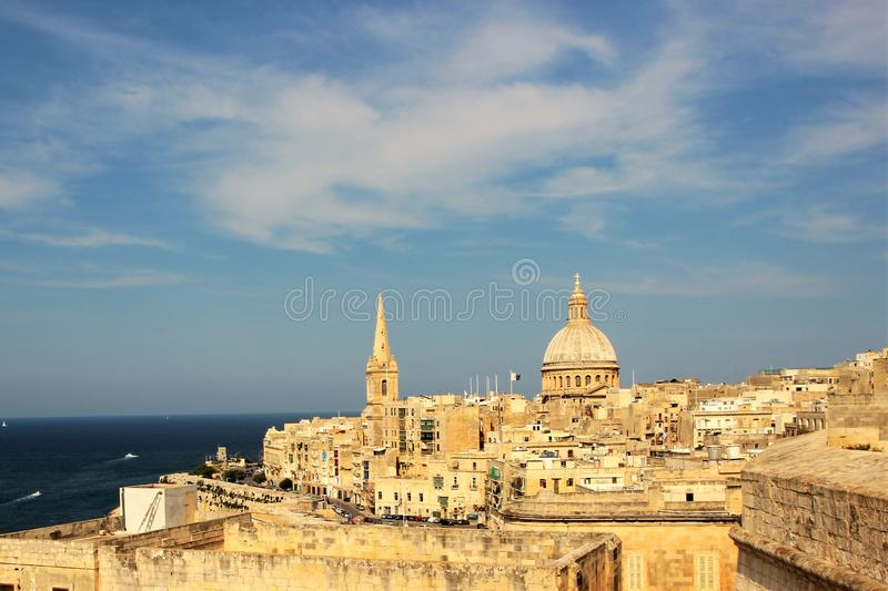Sky with clouds over the old capital of the island of Malta. Blue sky with light white clouds in contrast with the yellow Maltese stone buildings. Magnificent royalty free stock photography