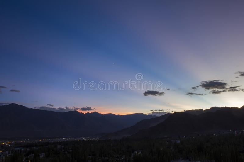 A blue sky lines on a pink sky with a star in the sunset sky over a city in a mountain valley royalty free stock image