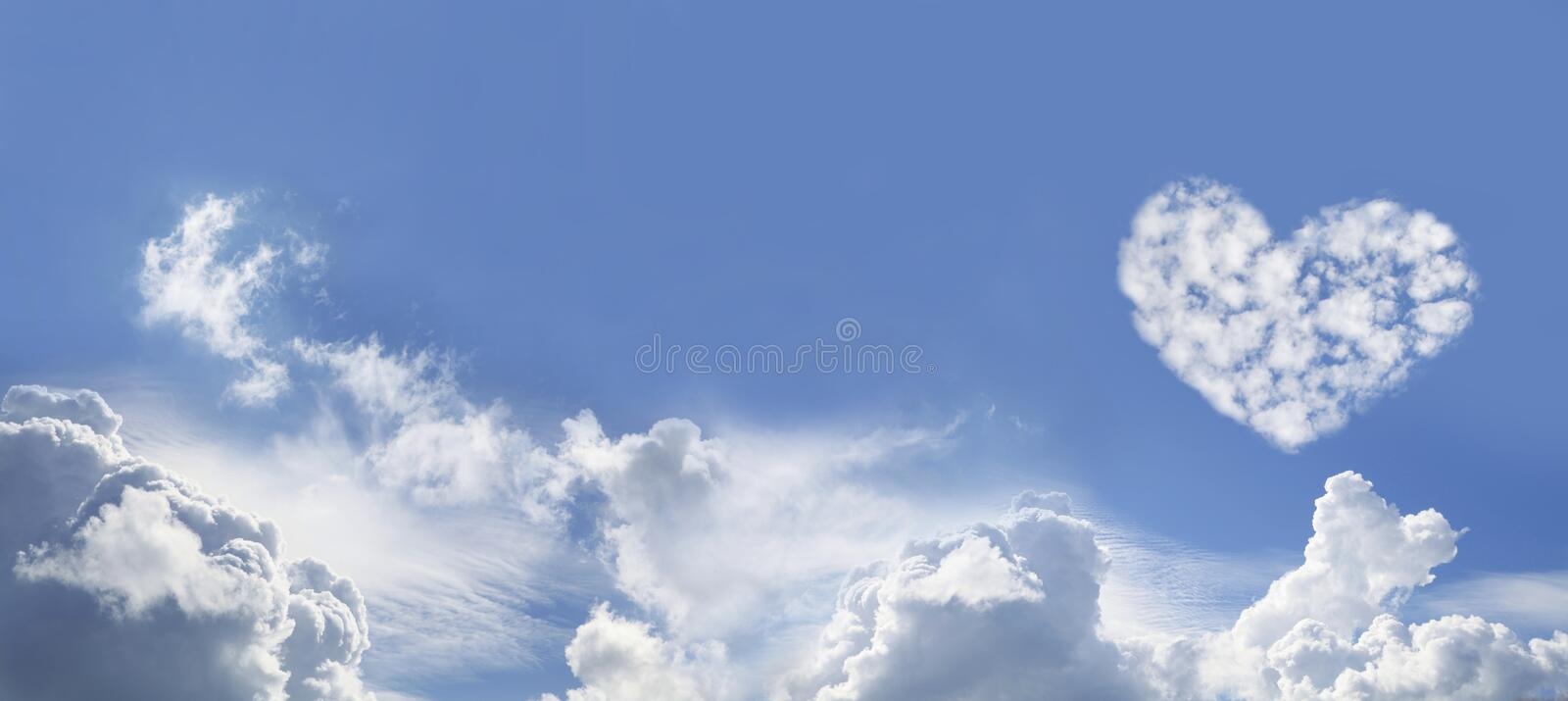 Blue Sky and Love Heart Shaped fluffy clouds. Wide Blue Sky Background with various fluffy clouds and one large Love Heart Shaped cloud formation on right hand stock images