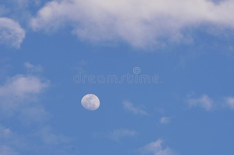 Blue sky with the moon and clouds stock photography