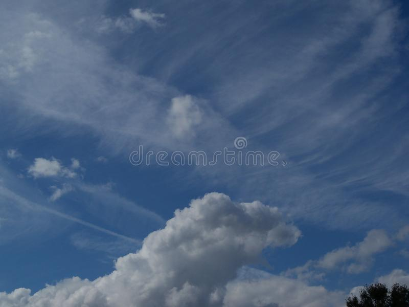Blue sky and multiple kinds of white clouds. Bright blue sky with different kinds of white clouds showing portents of the weather to come stock photography