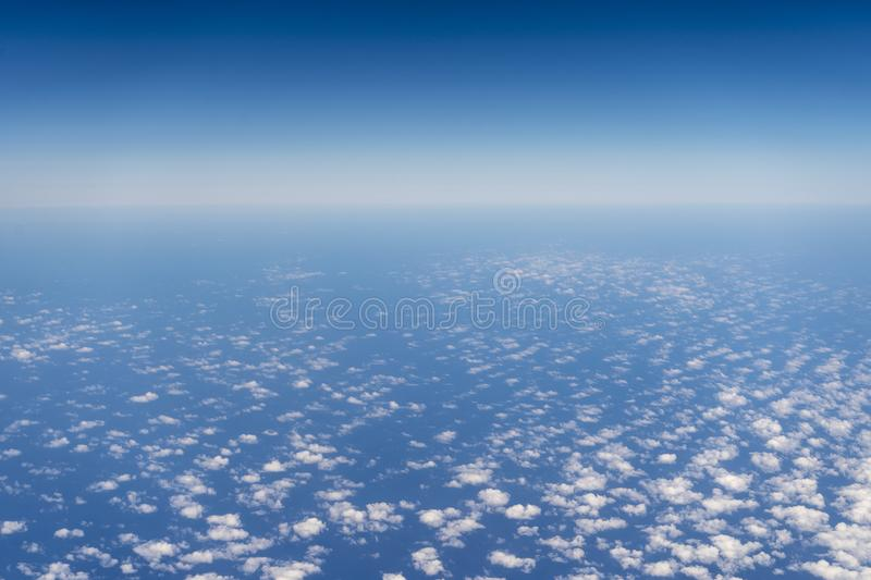 Blue sky and ocean seen from airplane stock photography