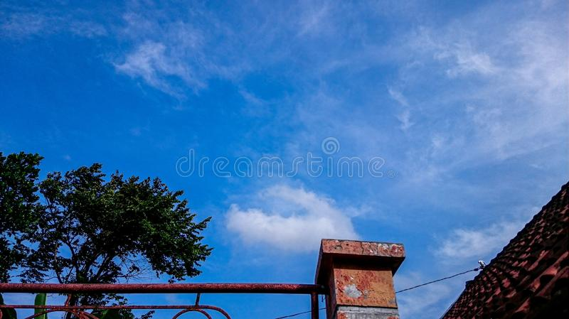 Blue sky with an old fences. Photo taken during the day with good weather and old fences, rooftop and view of wild tree royalty free stock photography
