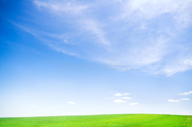 Blue sky over green field stock photos