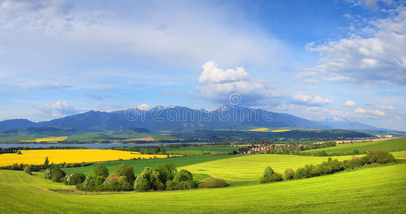 Blue sky over green meadow in mountain stock image