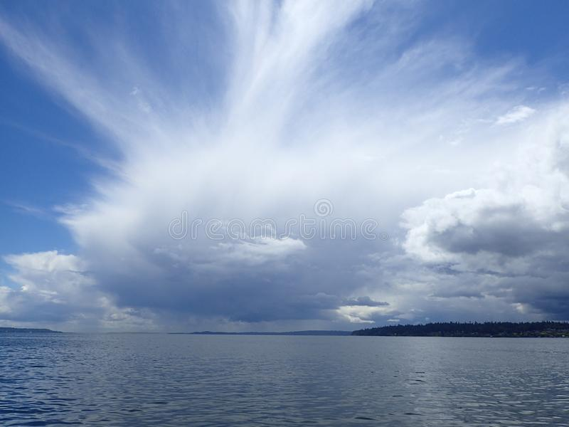 Blue Sky over Ocean with Storm. Blue skies over calm seas with storm clouds looming stock photography