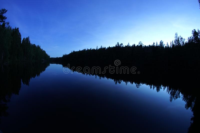 Blue sky over silent and still forest lake. Stars over silent and still forest lake. Night, scenery, landscape, water, trees, beautiful, relaxing stock image
