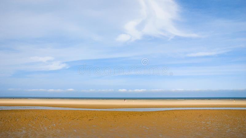 Blue sky over wet yellow sand beach Le Touquet royalty free stock photography