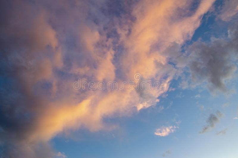 Blue sky with pink clouds in the glow of sunset royalty free stock photo