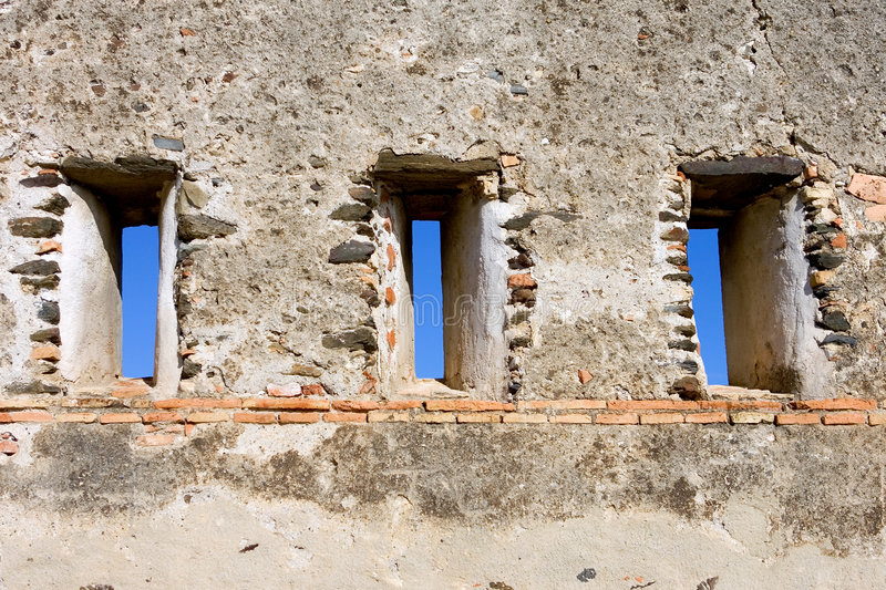 Blue sky poking through wall of castle in Spain. Blue sky peering through slit windows in wall of castle in Fuengirola Spain on the Costa del Sol royalty free stock photos
