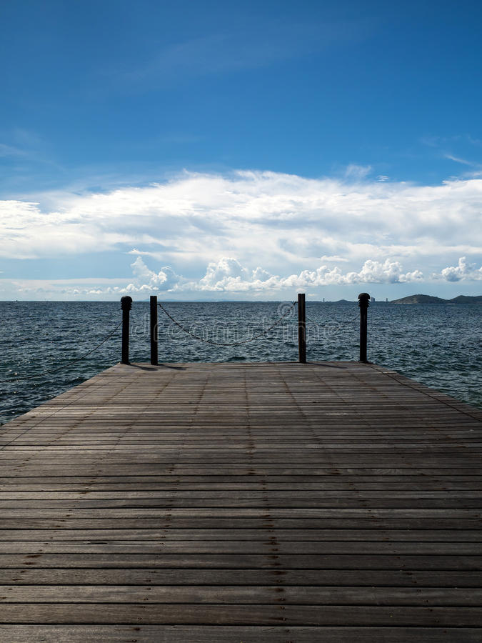 Blue sky and quiet deck by the sea in thailand. Sunny day blue sky quiet and private wooden deck on the remote island in Samed island royalty free stock photo