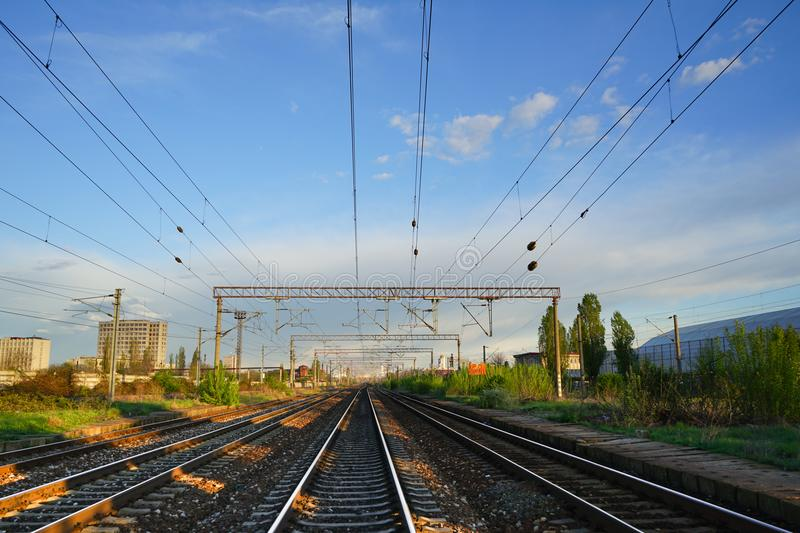 Blue sky and rails. Straight view of train rails under clear blue sky, Carpati statiion in Bucharest Romania, goldenhour royalty free stock photos