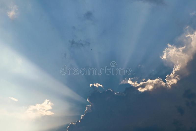 In the blue sky the rays of the sun come out from behind the clouds royalty free stock photography
