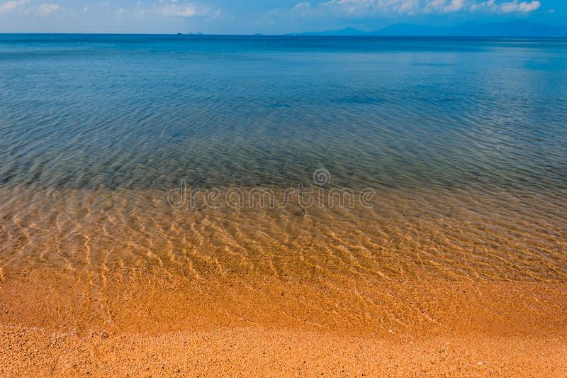 The blue sky is reflected in the clear water of the ocean. Blue water and yellow sand of Koh Samui beach. In the background you can see the neighboring island stock photography