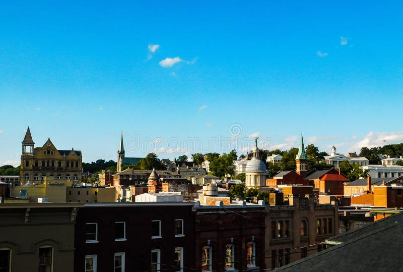 Blue Sky and Rooftops Over Staunton, Virginia. A view of rooftops, clouds, and blue sky over Staunton, Virginia during the day stock image