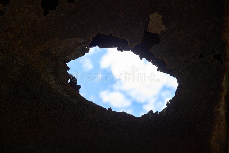 Blue sky through rusty hole stock photo