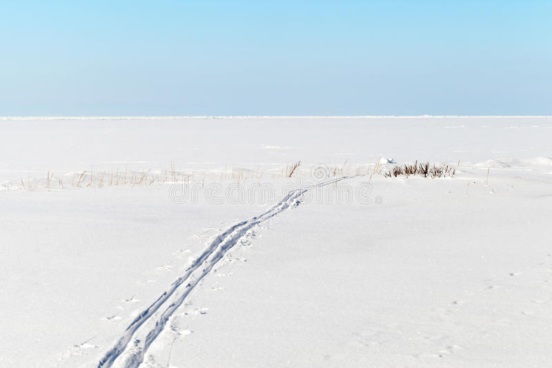 Blue sky, snow and Ski track on frozen sea. Blue sky, snow and Ski track crossing a frozen Baltic Sea. Winter sport - cross-country skiing stock photo
