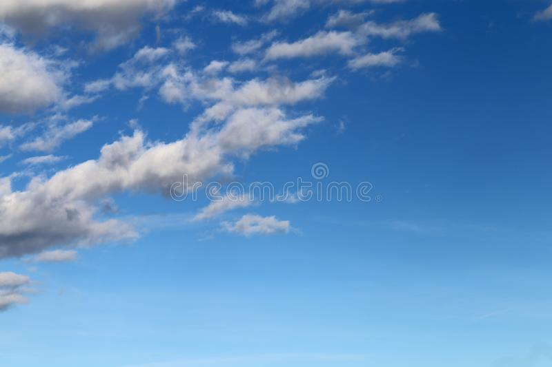 Blue Sky with Some Cotton Candy Clouds. Beautiful blue sky with some white cotton candy clouds during a sunny spring day. Very relaxing and lovely atmosphere stock photos