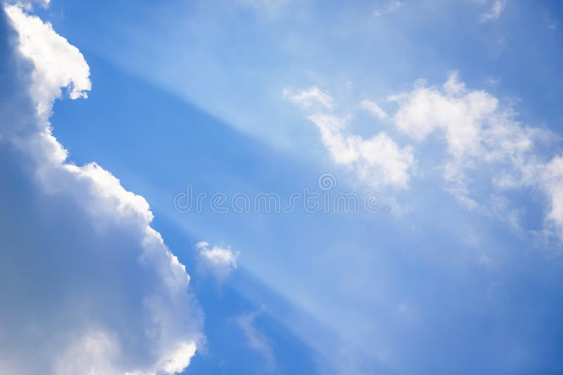 Blue sky with sun rays. Beam of light and the fluffy clouds royalty free stock image