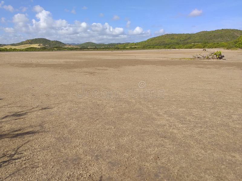 Panoramic photo of dry salt pans of ocher color. Blue sky with tropical clouds and mountains with vegetation. Martinique, French royalty free stock images