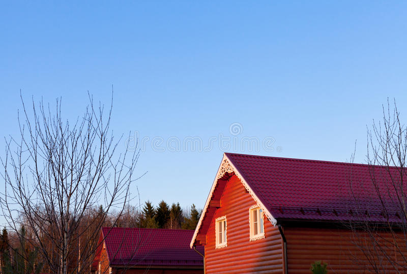 Blue sky under red tile roofs. Of new wooden houses in country village stock image