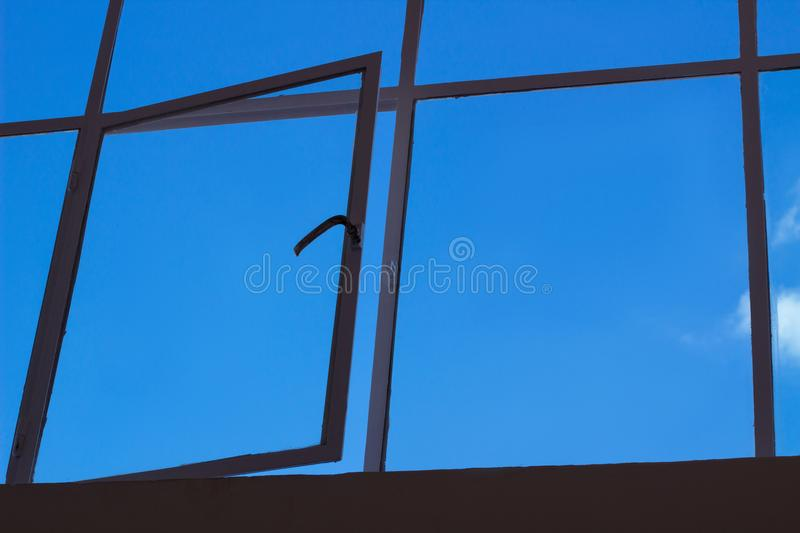 Blue sky view through upper glass window with open leaf royalty free stock images