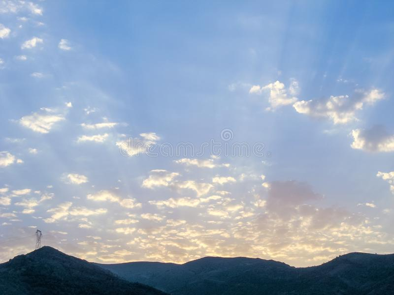 Blue sky with white cloud patches and mountains. Sun rays in the morning mountain sky stock photo