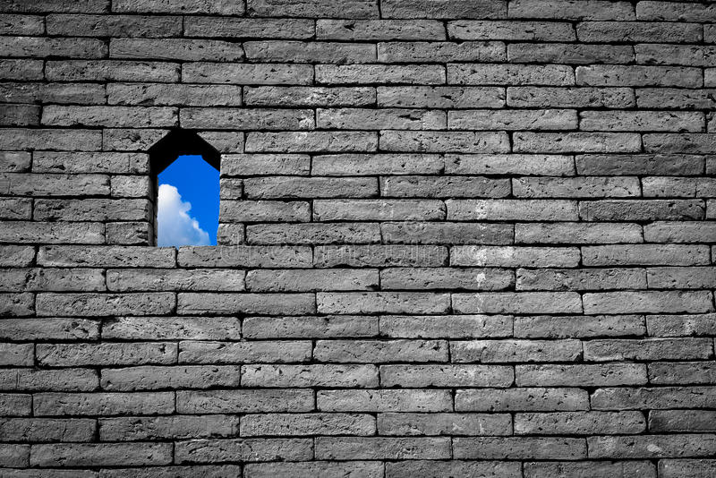 Blue sky with white cloud small window or hole on black and whit. E brick wall background freedom concept stock photo