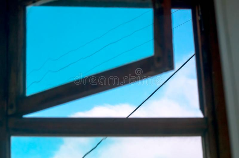 Blue Sky, White Clouds, Black Cables as Seen Looking Up the Open Window stock photography