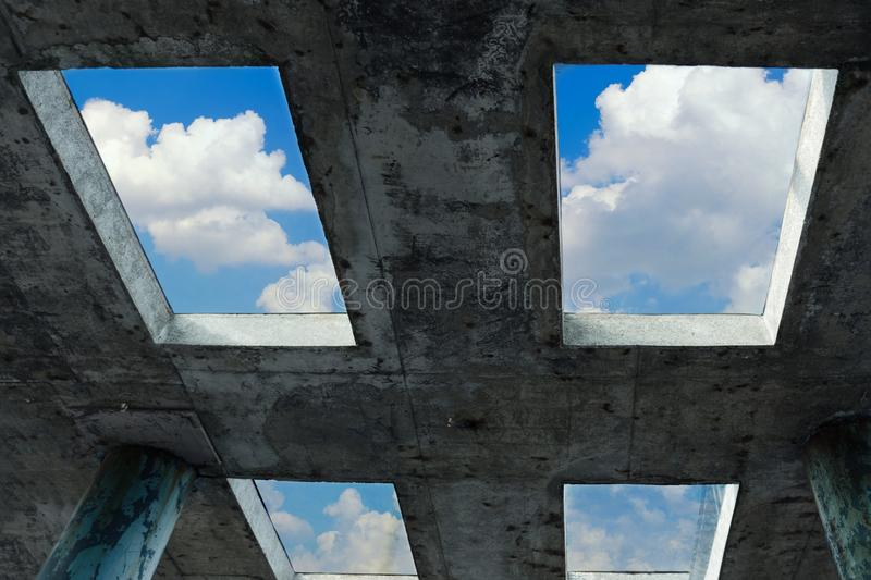 A blue sky with white clouds can be seen through the windows in a concrete building. The concept of faith, freedom and hope. Blue sky with white clouds can be royalty free stock photos