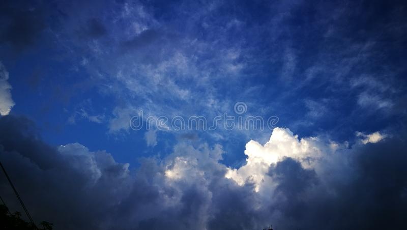 Blue sky with white clouds at the center surrounding by dark clouds. Environment, rainy, season, cloudscape, day, light, space, blank, nature, change stock photos