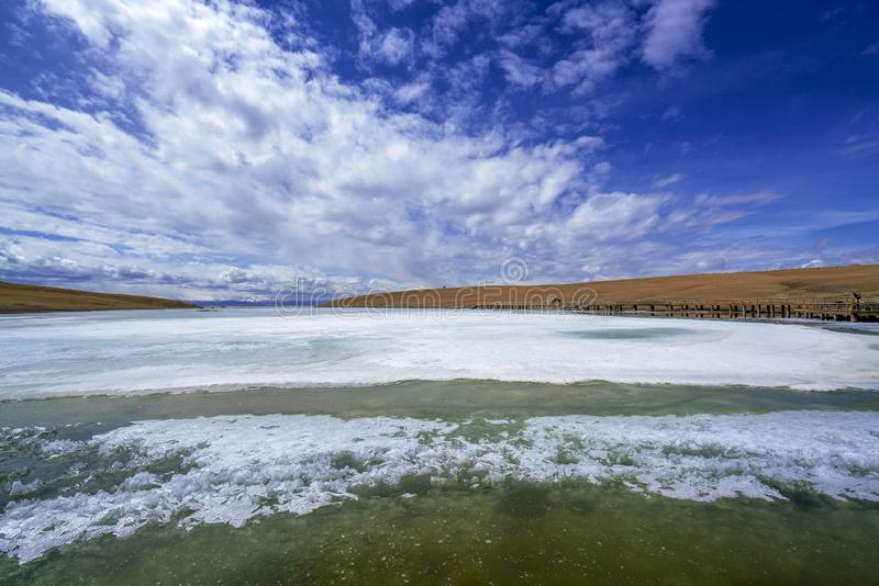 Blue sky white clouds Frozen river Yellow grass in Bayanbulak  in Spring stock image