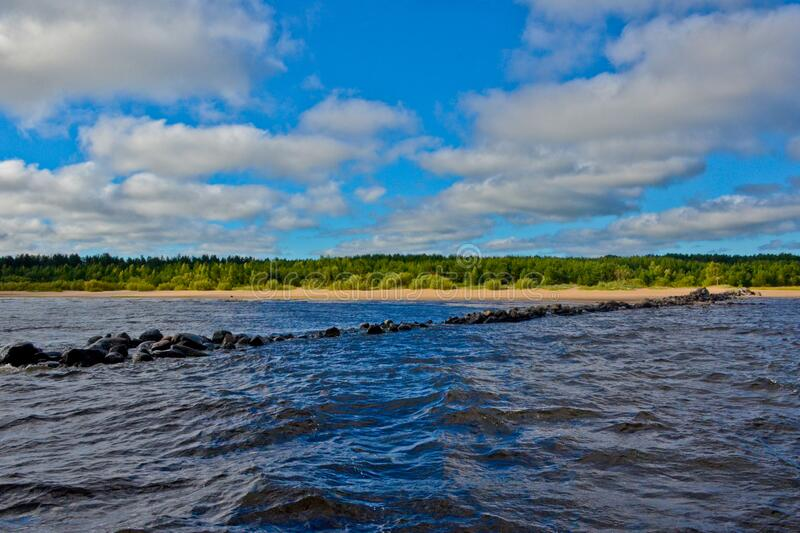 Blue sky and white clouds over Lake Ladoga. Dark water. A path made of stones in water. Little waves. On the horizon is a strip of land and forest royalty free stock photos