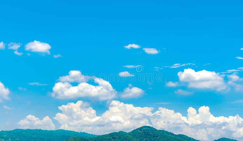 Blue sky and white cumulus clouds over green mountain. Beauty in nature. White fluffy clouds. Tropical nature. Sunny day royalty free stock photo