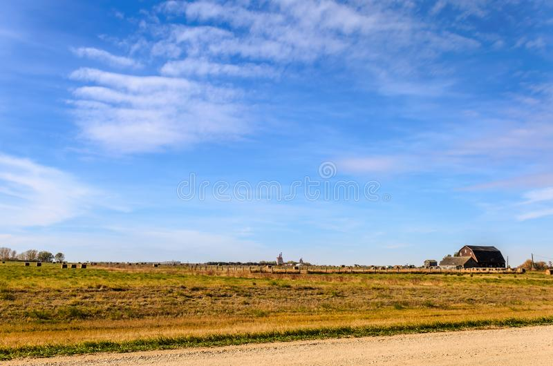 Blue sky with white, fluffy, tender cirrus clouds, yellow field, green grass, grain current, haystacks stock photos