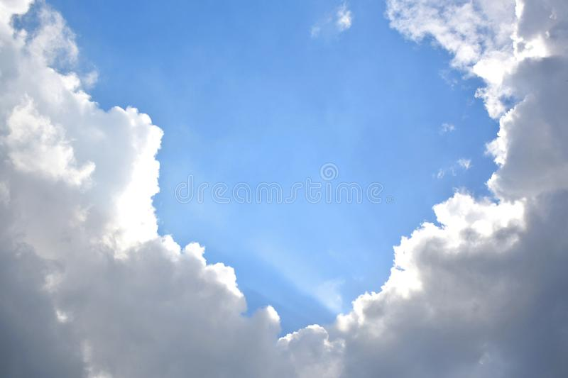 Blue sky with white and grey clouds. While the sun rays are passing by stock images