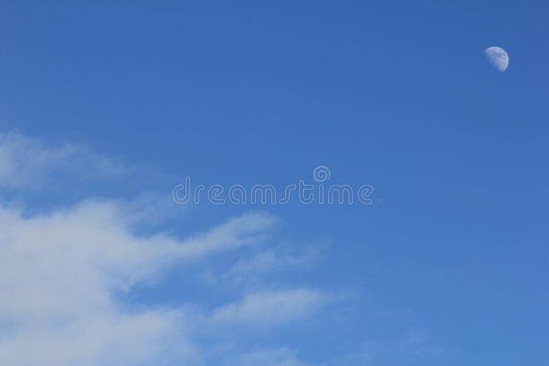 Blue sky and white half moon and white clouds royalty free stock photos