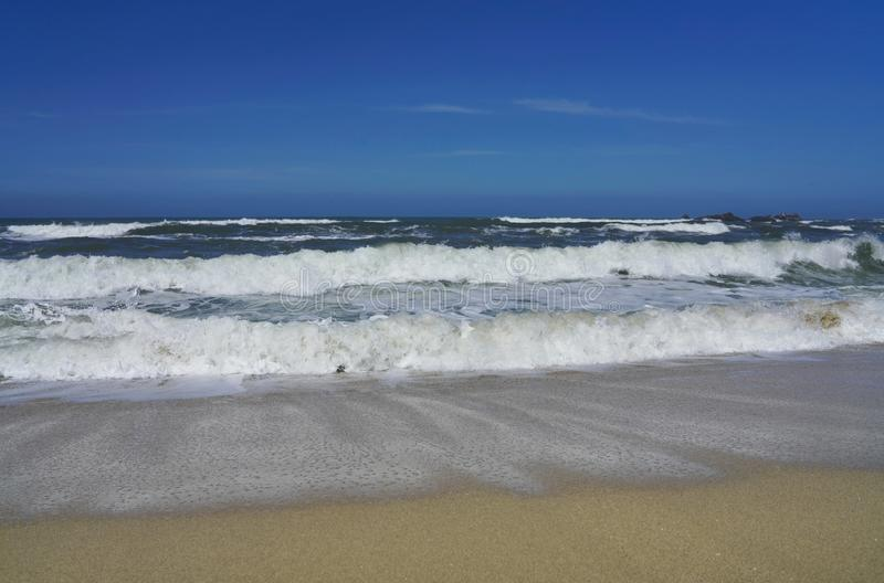 Blue sky, white waves and sunshine sandy beach at Pacific Coast royalty free stock photo