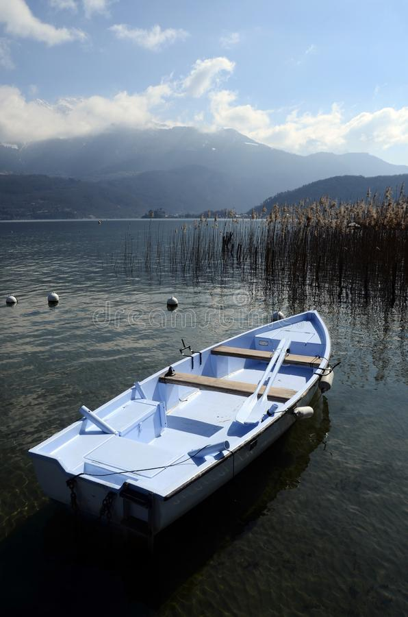 Blue small boat on Annecy lake stock image