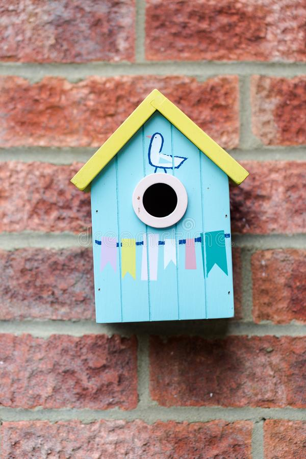 Blue small cue wooden bird house hanged on brick wall stock photo