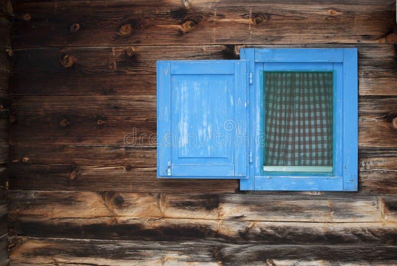Blue small window. Blue window on a wooden hut stock image