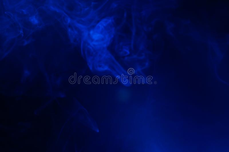 Blue smoke on black background. Abstract, air, aroma, art, burning, cigarette, color, concept, creativeness, curve, delicate, design, detail, dynamic, effect stock image