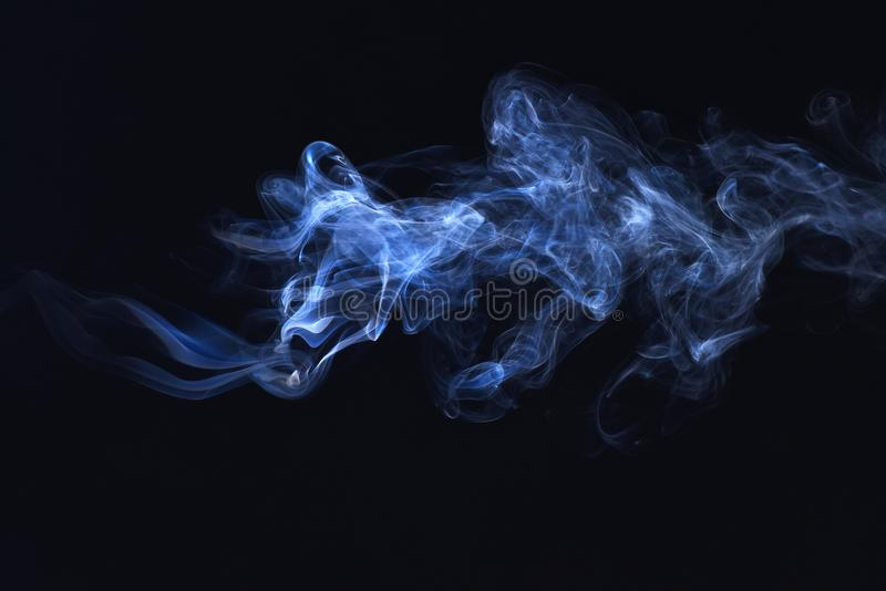 Blue smoke on black background, freeze motion of powder explosion stock images
