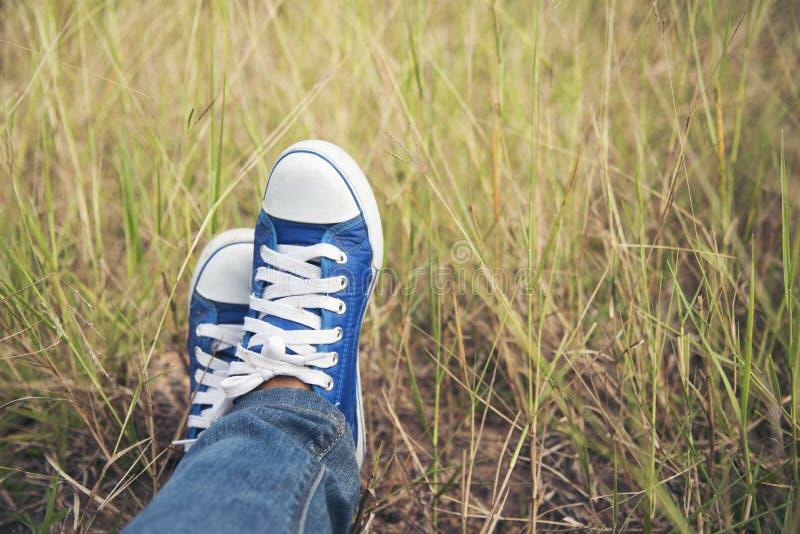 Blue sneaker, Pretty woman wear jeans and a blue sneaker on a green meadow royalty free stock photo