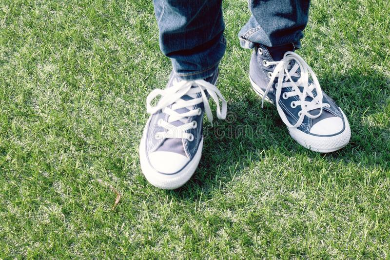 Blue sneakers on a kids feet outdoors royalty free stock images