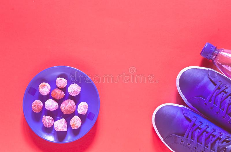 Blue sneakers and kumquat energy balls on the background the trend colour of the year 2019, Living Coral. royalty free stock image
