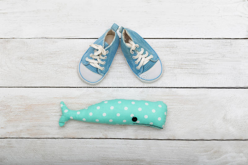 Blue sneakers for a small child and a toy on a wooden background stock photos