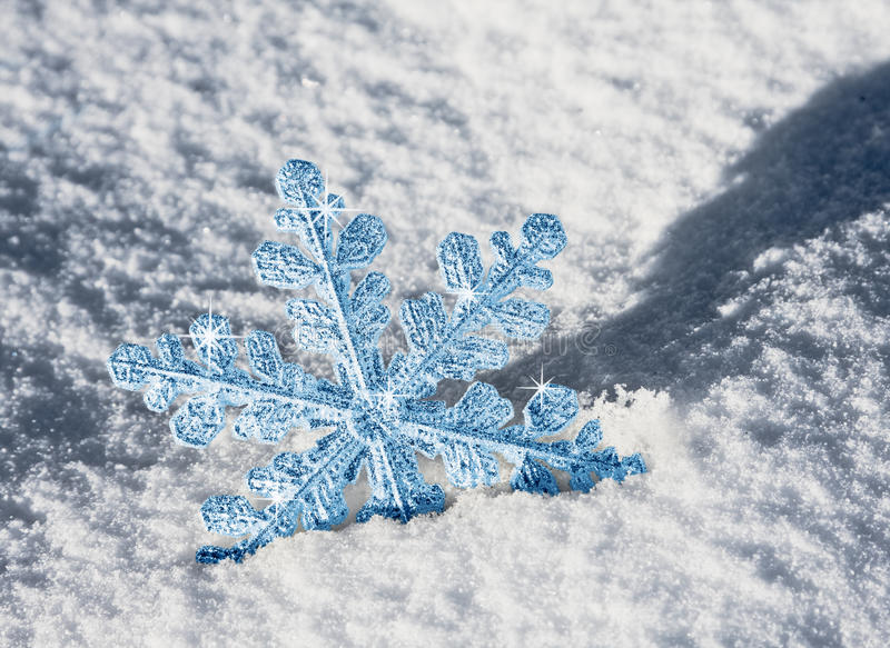 Blue snowflake. Lies in the snow royalty free stock image